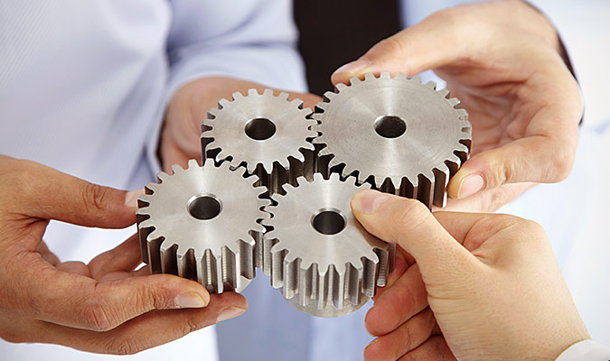 The hands of two men and a woman can be seen collectively holding a set of four connected gears.