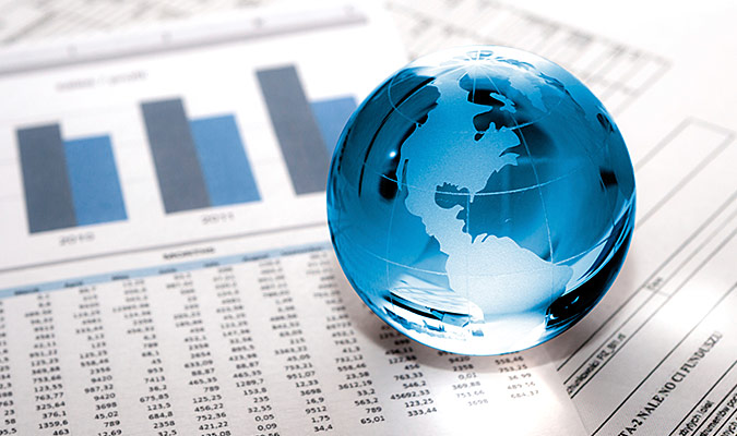 Miniature blue globe of the world sits atop a stack of business memos.