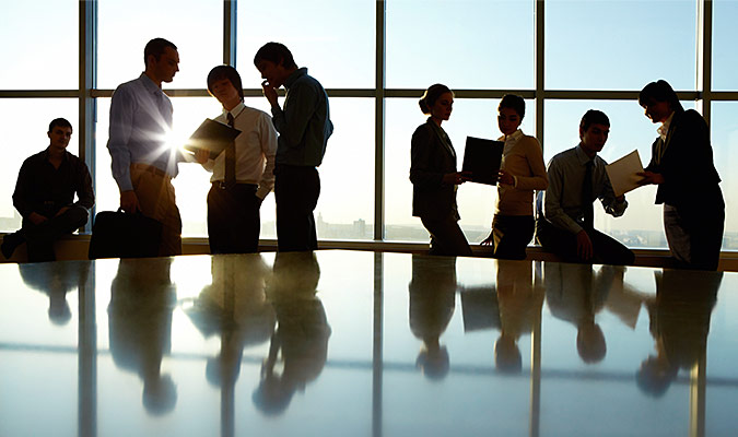 Young professionals gathered in groups at a meeting to discuss shared memos.