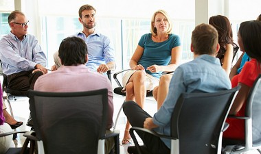 A group of about ten people sat in a circle conducting a business meeting.