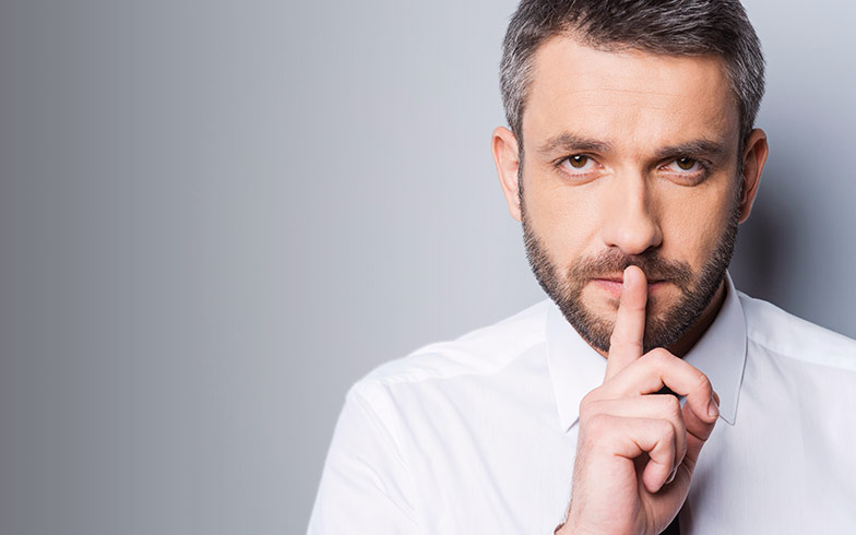 Young man making a shhh gesture