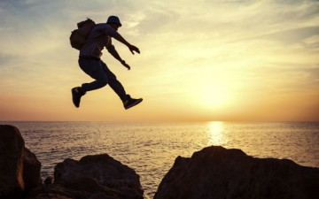 Image of a man jumping from rock to rock