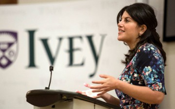 Image of a woman speaking into a microphone with an Ivey banner in the background