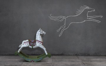 Image of a rocking horse looking at a drawing of a horse flying