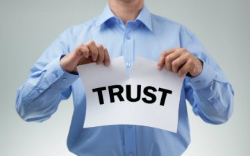 """Image of a man ripping a paper that says """"trust"""""""