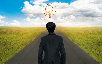 An image of a man on a road with a lightbulb over his head