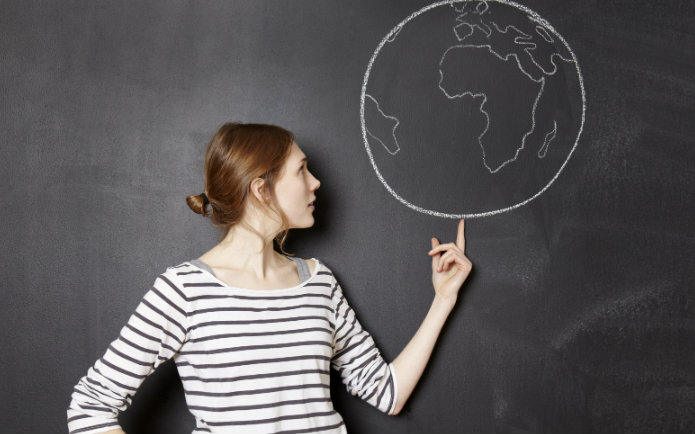 A woman standing in front of a blackboard pointing to a drawing of the earth