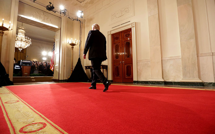 Image of President Donald Trump walking on a red carpet into the East Room
