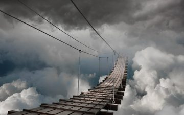 An image of a bridge leading into a stormy sky
