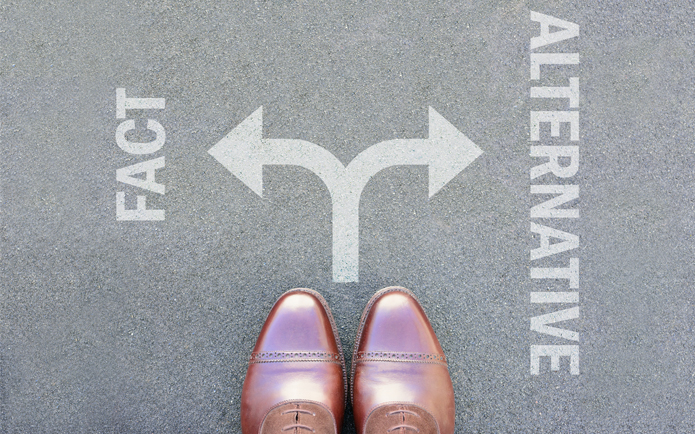 A pair of shoes at a crossroads, one side labelled fact and one side labelled alternative