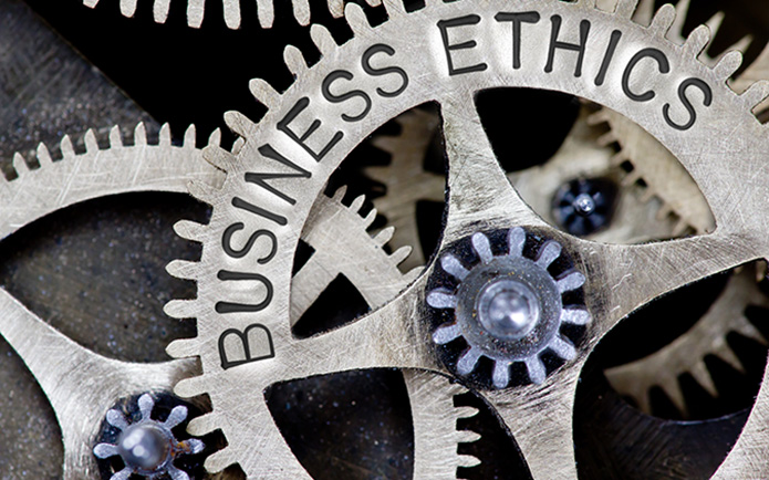 Macro photo of tooth wheel mechanism with BUSINESS ETHICS concept letters