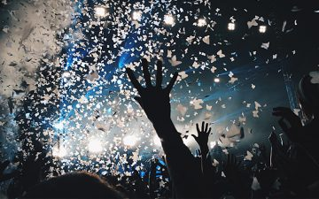 A crowd at a concert with confetti falling from the ceiling