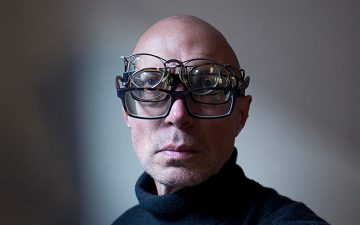 A man wearing multiple pairs of glasses