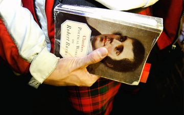 Image of a person holding a collection of poetry by Robert Burns