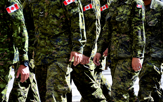 Image of Canadian soldiers wearing green camouflage marching together
