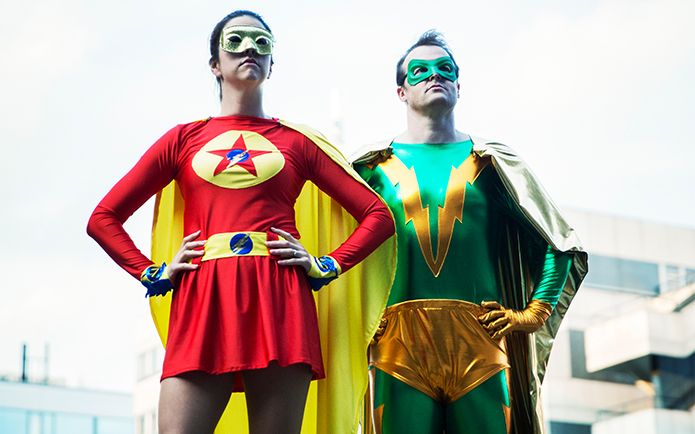 A woman and a man dressed as superheroes