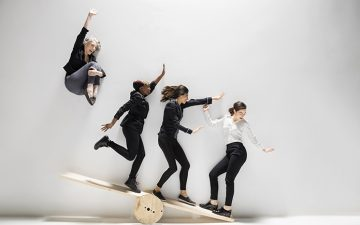 Four women balancing on a wooden teeter-totter