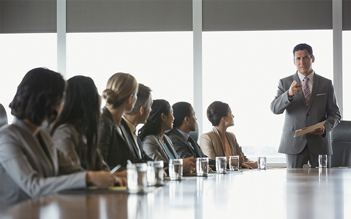 Image of a serious looking man standing at the head of a table conducting a business meeting