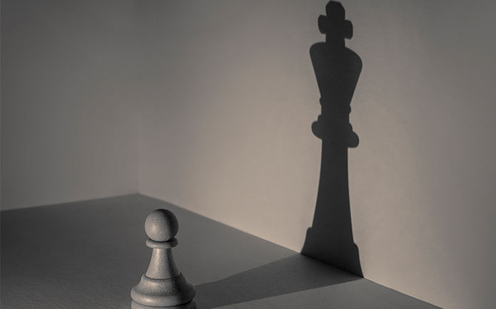 Chess pawn piece casting the shadow of a chess king piece