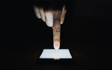 Close up of woman's hand using smartphone in the dark