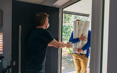 Man delivering huge pile of toilet rolls to customer in mask