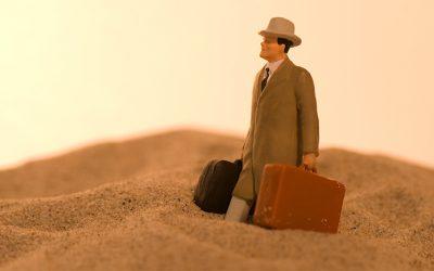 Plastic businessman walking through quicksand.