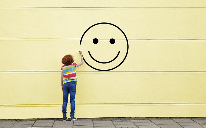 Girl drawing smiley face on to a wall.