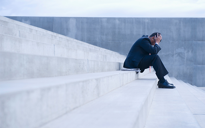 Frustrated Hispanic businessman sitting on steps