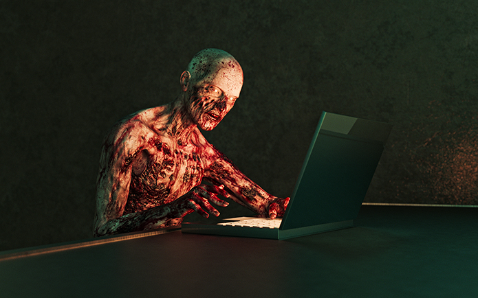 Horror Zombie with flaking flesh using laptop computer in dark room.